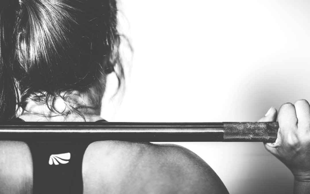 Athlete lifting a barbell behind her neck in a coached training session