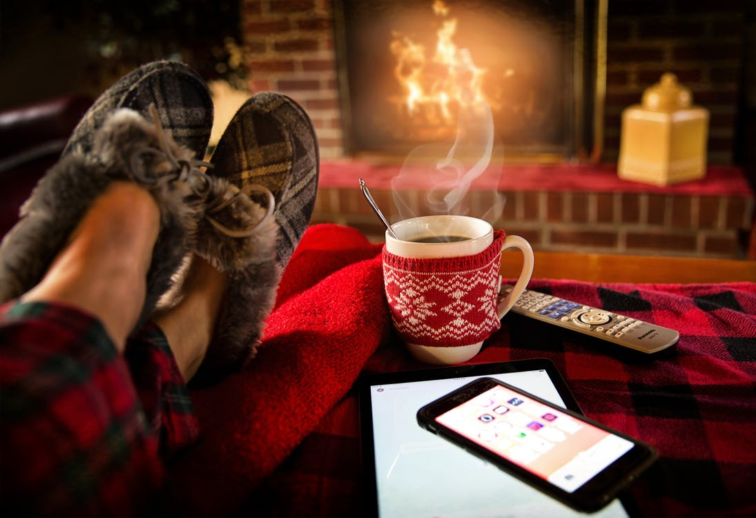 Lots of technology on a table in front of a warm fire